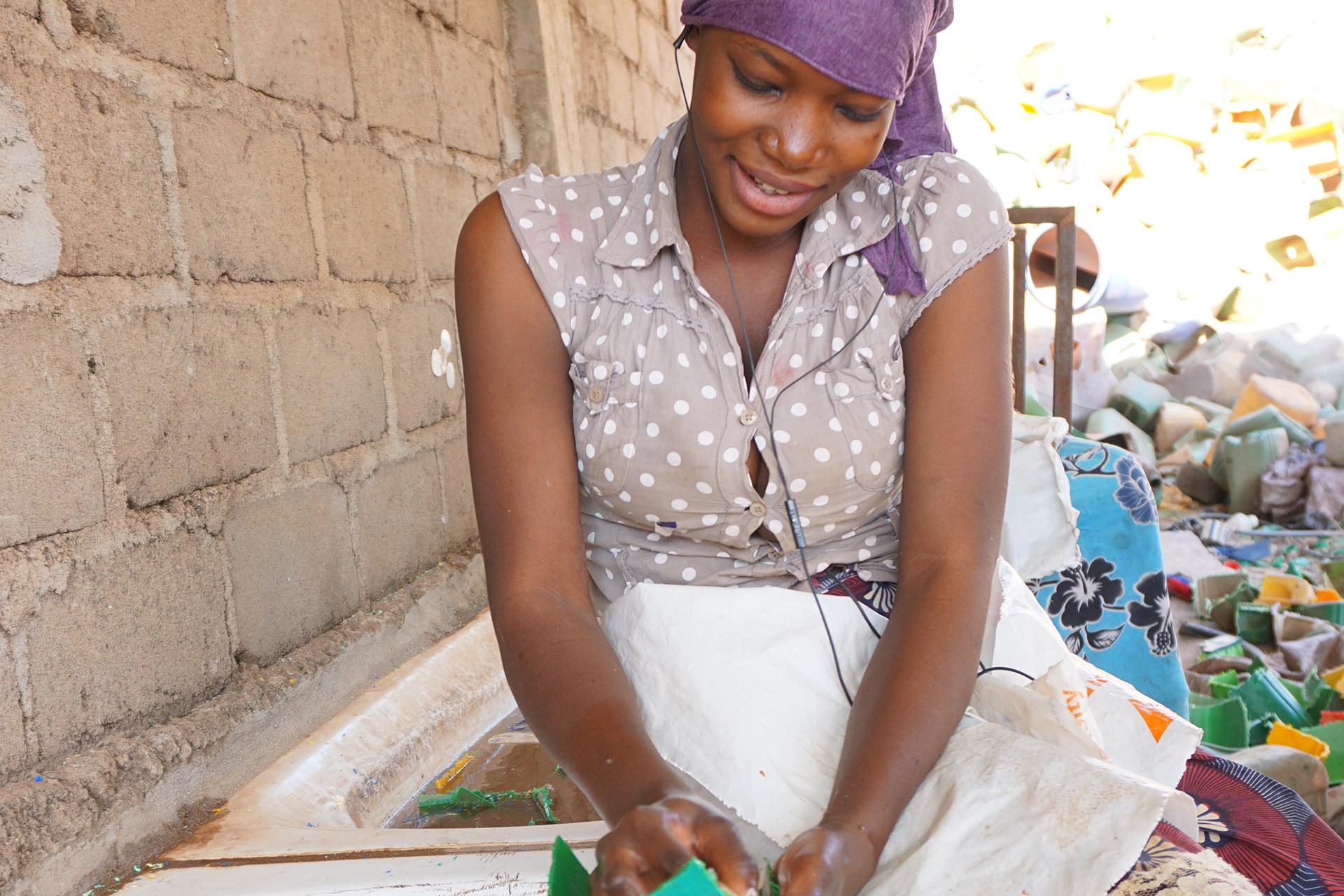 Kvinne som har fått jobb og vasker plast