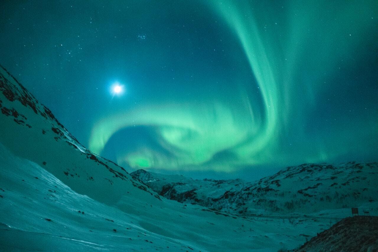 Nordlys og måne skinner over vinter og fjellandskap